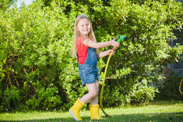Beautiful blond girl watering flowers, lawn on a sunny beautiful