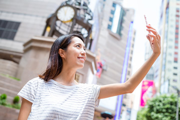 Woman taking phone by cellphone in Causeway bay of Hong Kong
