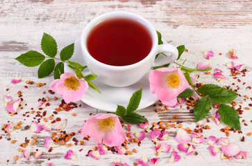 Cup of tea with wild rose flower on old rustic wooden background