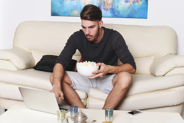 Young man eating popcorn and using laptop