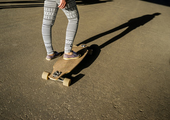 Young girl riding on a longboard in city