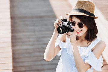 Young beautiful woman photographer taking images with camera
