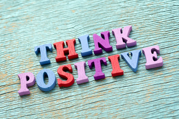 Think positive phrase on vintage wooden background