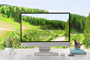 Conceptual image of a work space and computer desktop with tall green trees over blue sky background