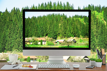 Conceptual image of a work space and computer desktop with small village in mountains