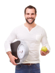 Happy man with scale weight and green apple