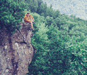 Traveler sitting on top of cliff and drinking tea