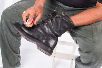 Man cleaning combat shoes