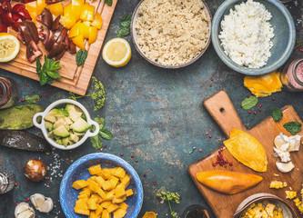 Quinoa salad ingredients: tomatoes, avocado , mango , garlic , feta cheese,lemon, oil. Quinoa salad preparation on dark rustic background, top view, frame. Superfood, healthy Eating food concept