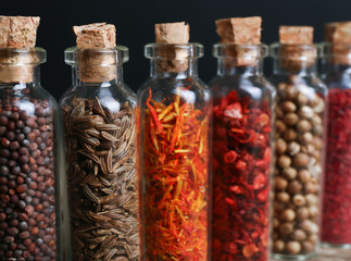 Different spices in small glass bottles, close-up
