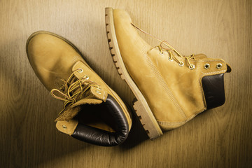 Pair of old yellow working boots Isolated on wood background