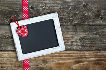 Photo frame with small heart and ribbon on rustic wooden wall with copy space