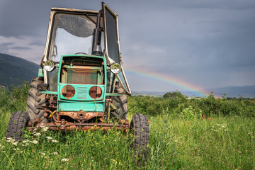 Fototapete - old tractor on the grass field