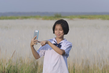 Thai girl student taking selfie at the white meadows