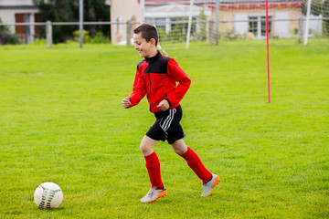 Little Boy playing soccer on the sports field.Training little boy on a asport field.Boy running with a soccer ball on a country sport field .