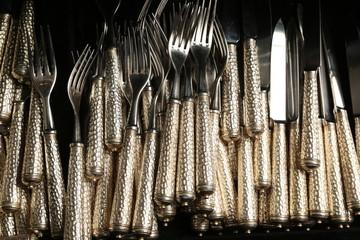 Knifes and forks arrange on a full dark background.
