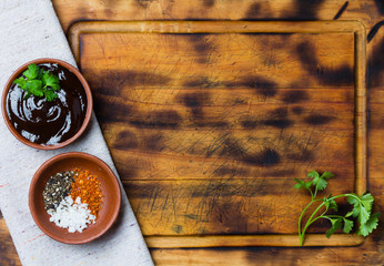 Barbecue sauce, salt, black and red pepper on cutting board