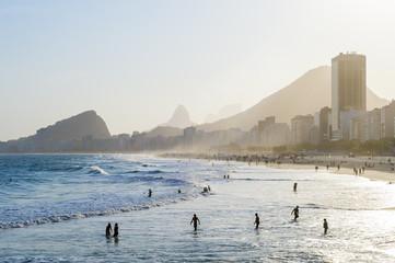 Silhouettes wading in the shallows of Copacabana Beach as the sun sets behind the Rio de Janeiro, Brazil skyline