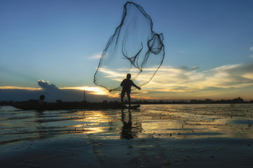 Traditional Asian fishermen throwing net fishing in the river at sunset time.