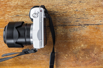 white mirrorless camera on wooden table with copy space.
