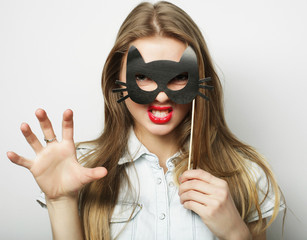 Playful young woman holding a party mask