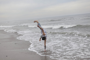 A young man doing a handstand on the beach