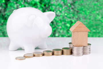 Wooden block houses, coins and a piggy bank: home budget