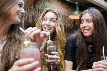 Happy young friends enjoying drinks at a bar