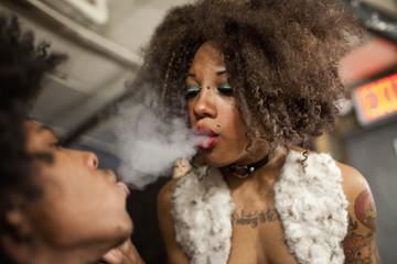 Young couple blowing smoke