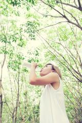 Portrait of young beautiful  woman wearing white dress drinking
