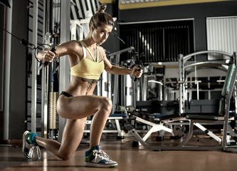 young fitness woman execute exercise with exercise-machine Cable