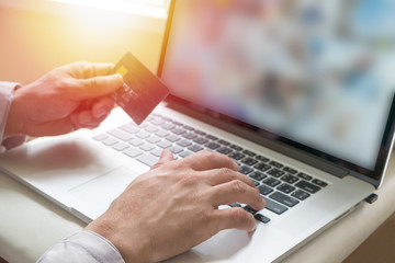 Man holding credit card on laptop for online shopping
