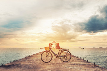 Vintage bicycle on concrete pier in sunset, vintage tone, soft focus