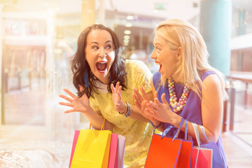 Excited and happy best friends shopping together