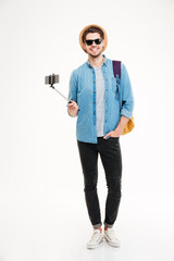 Smiling man with backpack and mobile phone on selfie stick