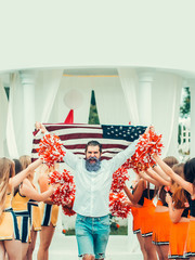 man with american flag and cheerleader team