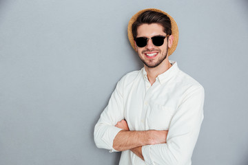 Cheerful man in hat and sunglasses standing with hands folded