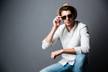Portrait of confident young man in hat and sunglasses Wall mural
