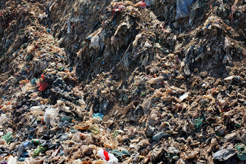 Bali, Indonesia - April 30, 2016: Plastic bags, household garbage and toxic industrial waste contaminates land, soil and groundwater at a landfill site in Bali, Indonesia.