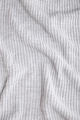 Full page close up of a grey knitted jumper