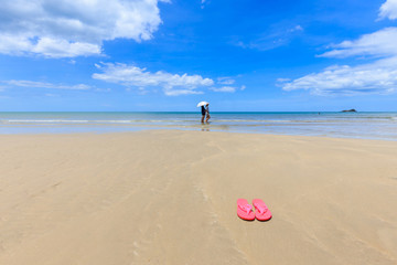 Pink sandals on the beautiful beach