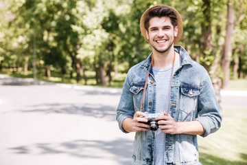 Happy young man in hat with old vintage photo camera