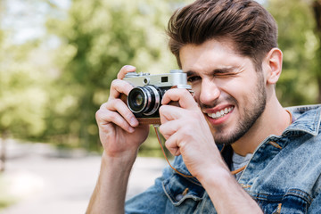 Close-up portrait of casual man making photo using camera