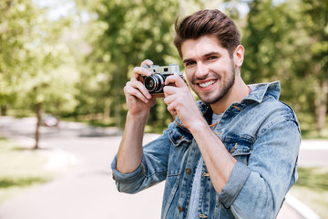 Happy casual man making photo on camera