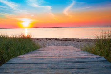 Wall Mural - Wooden beach path to sand and sea at sunset