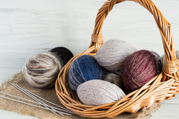 Balls wool yarn in a basket.    Balls wool yarn in a wicker basket and knitting needles on a burlap on a light wooden background.