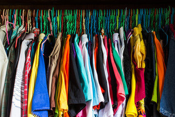 messy closet overfilled with colorful woman clothes on hangers a