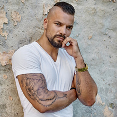 Tattooed brutal man outdoor fashion portrait