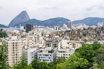 Gritty urban overlook of the Rio de Janeiro city skyline with Sugarloaf Mountain looming over residential apartments and a nearby favela adjacent to the hillside Santa Teresa neighborhood