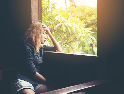 Women lifestyle concept : young sad woman sitting on bench besid